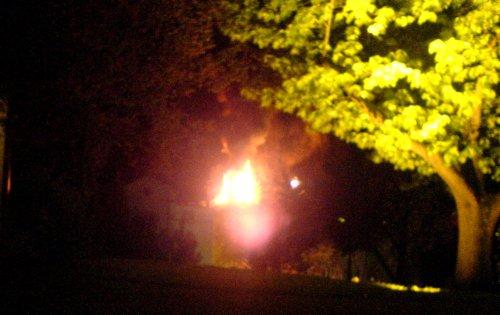 Das Feuer aus der Ferne; im Vordergrund der Mensahügel. Die kleine Lichtquelle neben den Flammen gehört zu der Drehleiter, von der aus die Feuerwehr löschte.