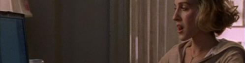 Carrie Bradshaw sitzt vor ihrem Mac.
