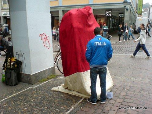 Aufgabaut wird die Skulptur jeden Morgen hinter einem roten Vorhang. Im Bild: Der Ingenieur des Projekts, offenbar ein Herr aus Italien.