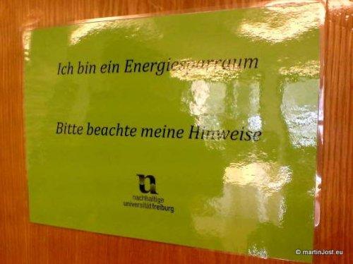 Schild: Ich bin ein Energiesparraum. Bitte beachte meine Hinweise. Nachhaltige Universität Freiburg