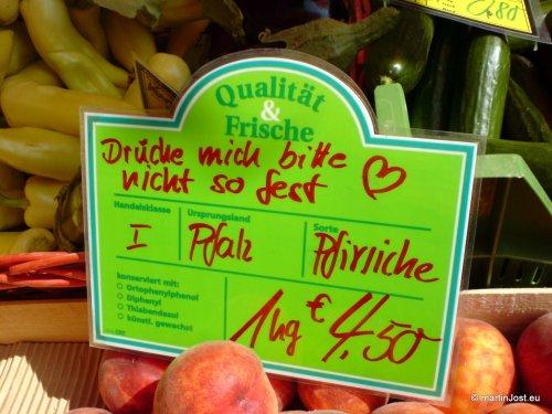 Preisschild am Obststand auf dem Markt. Die Pfälzer Pfirsiche sagen: Drücke mich bitte nicht so fest -- Herz-Emoticon.